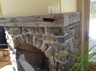Reclaimed Beam Mantle with Rounded Stone Fireplace