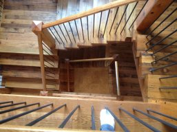 Downward view of these natural grade Reclaimed Oak Staircase outfitted with custom treads, handrails and newel posts.