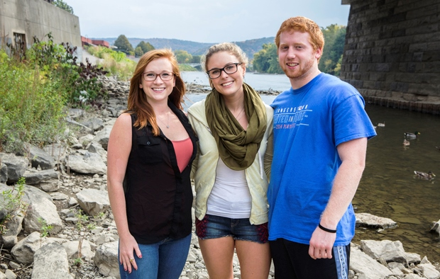 Binghamton University students Megan Burney, left, Danielle Robinson and Jake Geiger saved the life of an autistic girl in September when the child wandered into the river in the City of Binghamton where they are standing. Photo by Jonathan Cohen