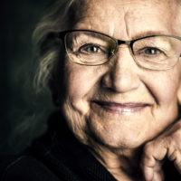 Portrait of a beautiful senior woman in elegant glasses smiling at camera.