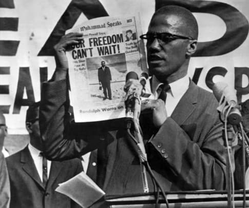 1_Malcolm X (1925 - 1965) holds up an issue of the Muhammad Speaks newspaper during a rally, New York, New York, July 27, 1963. (Photo by Underwood Archives:Getty Images)
