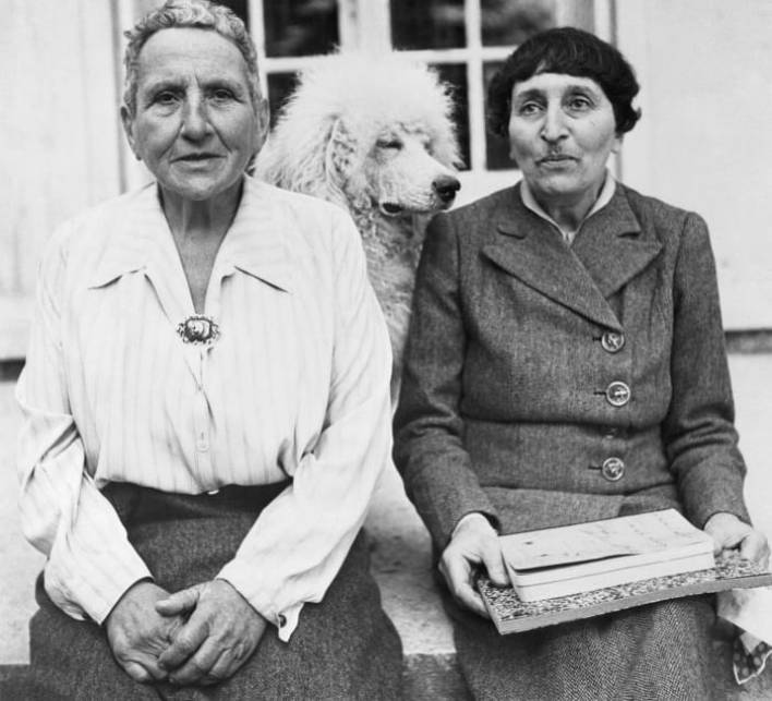 Gertrude Stein and Alice B. Toklas with their dog Basket in front of her home in France