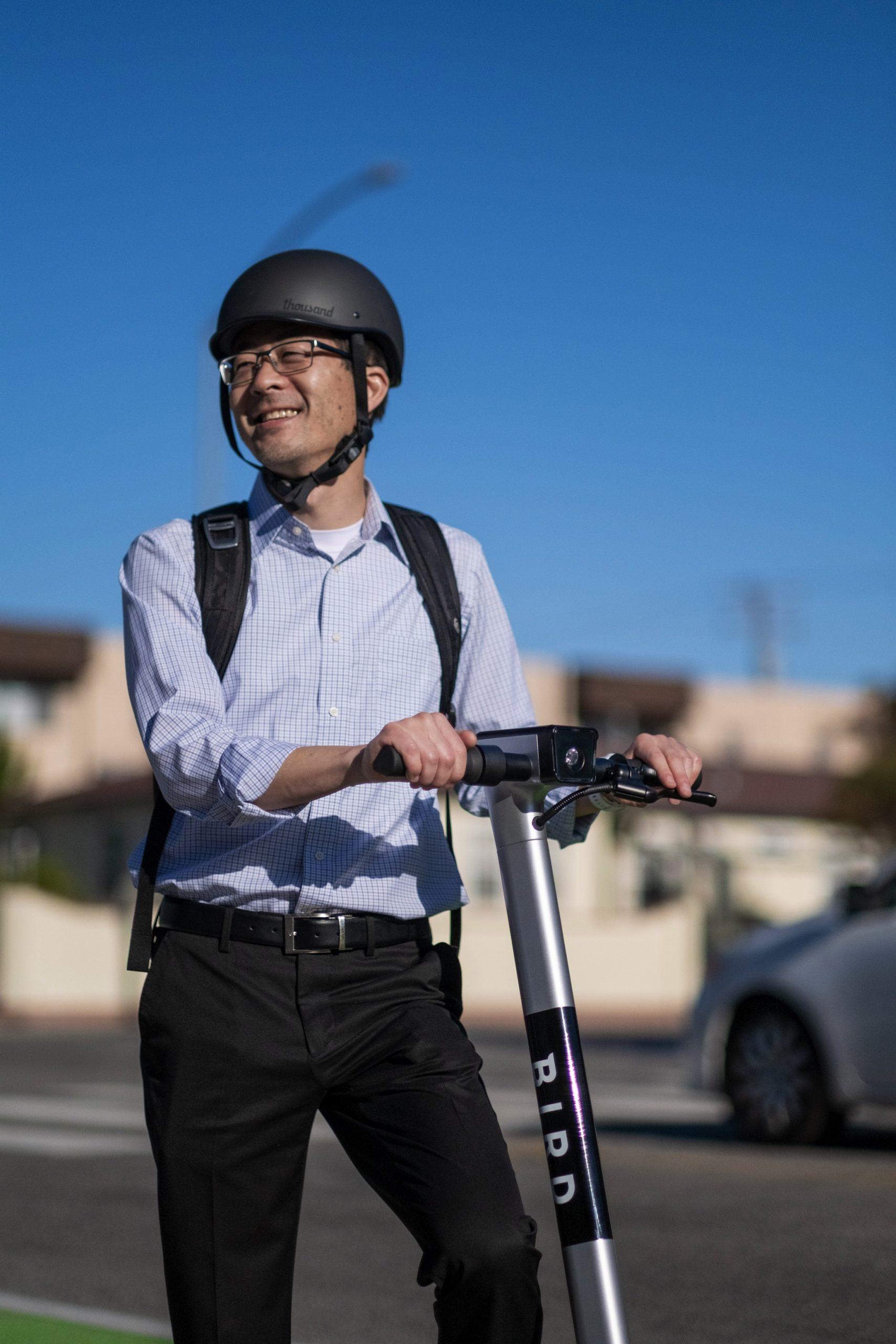 Man wearing Bird helmet and backpack, holding handlebars of Bird scooter