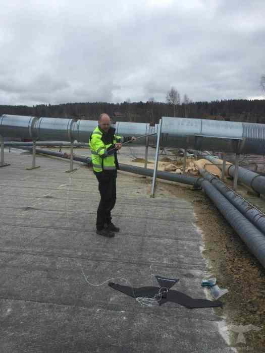 Flygande fågelskrämma drake monterad på industritak i Leksand