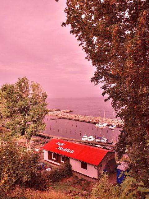 Bild: Der Hafen von Lohme auf der Insel Rügen mit dem Cafe Niedlich. OLYMPUS OM-D E-M5 mit M.ZUIKO DIGITAL ED 12‑40mm 1:2.8. ISO 200 ¦ f/7,1 ¦ 12 mm ¦ 1/2500 s ¦ kein Blitz ¦ 8 Einzelbilder. Klicken Sie auf das Bild um es zu vergrößern.