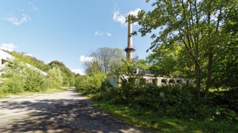 Bild: Schornstein des zentralen Heizkraftwerkes aus der Zeit des 18. Marinepionierbataillon der NVA auf dem ehemals militärisch genutzten Areal des Schlosses Dwasieden in der Nähe des Hafens von Sassnitz. Links ist das Gebäude der Werkstatt zu sehen. Klicken Sie auf das Bild um es zu vergrößern.