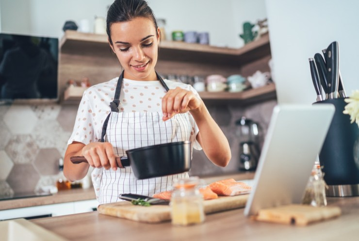 Young woman using digital tablet while cooking salmon fillet in the kitchen