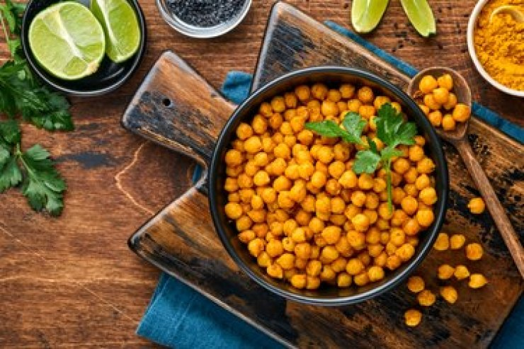 Fried chickpeas with turmeric in ceramic plate on an old wooden table background.  View from above.