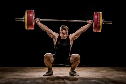 Men exercise with barbells