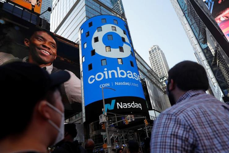 People watch as the logo of Coinbase Global Inc, the largest U.S. cryptocurrency exchange, is displayed on the Nasdaq MarketSite jumbotron in Times Square in New York, United States, on April 14, 2021.  REUTERS / Shannon Stapleton