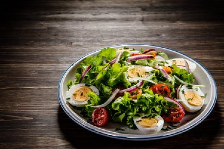 Boiled eggs and colorful vegetables on a white plate on a wooden background