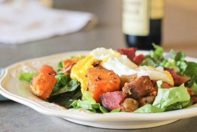 Warm breakfast salad on a white plate with fried eggs and diced sweet potatoes
