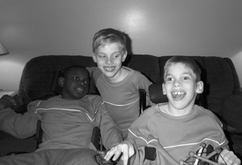 Anthony, Aaron and Eric, all 8 years old,  playing in their living room.