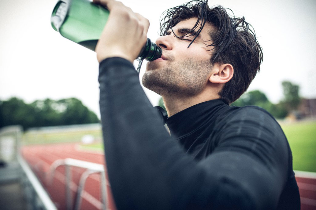 Athletic young man drinking a bottle of water