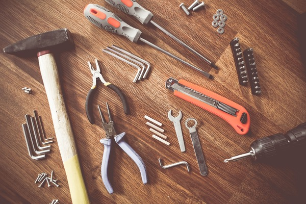 Table top with tools including pliers, wrench, screwdrivers and bits.