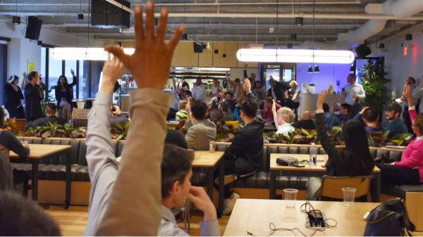 People at a conference raising their hands.