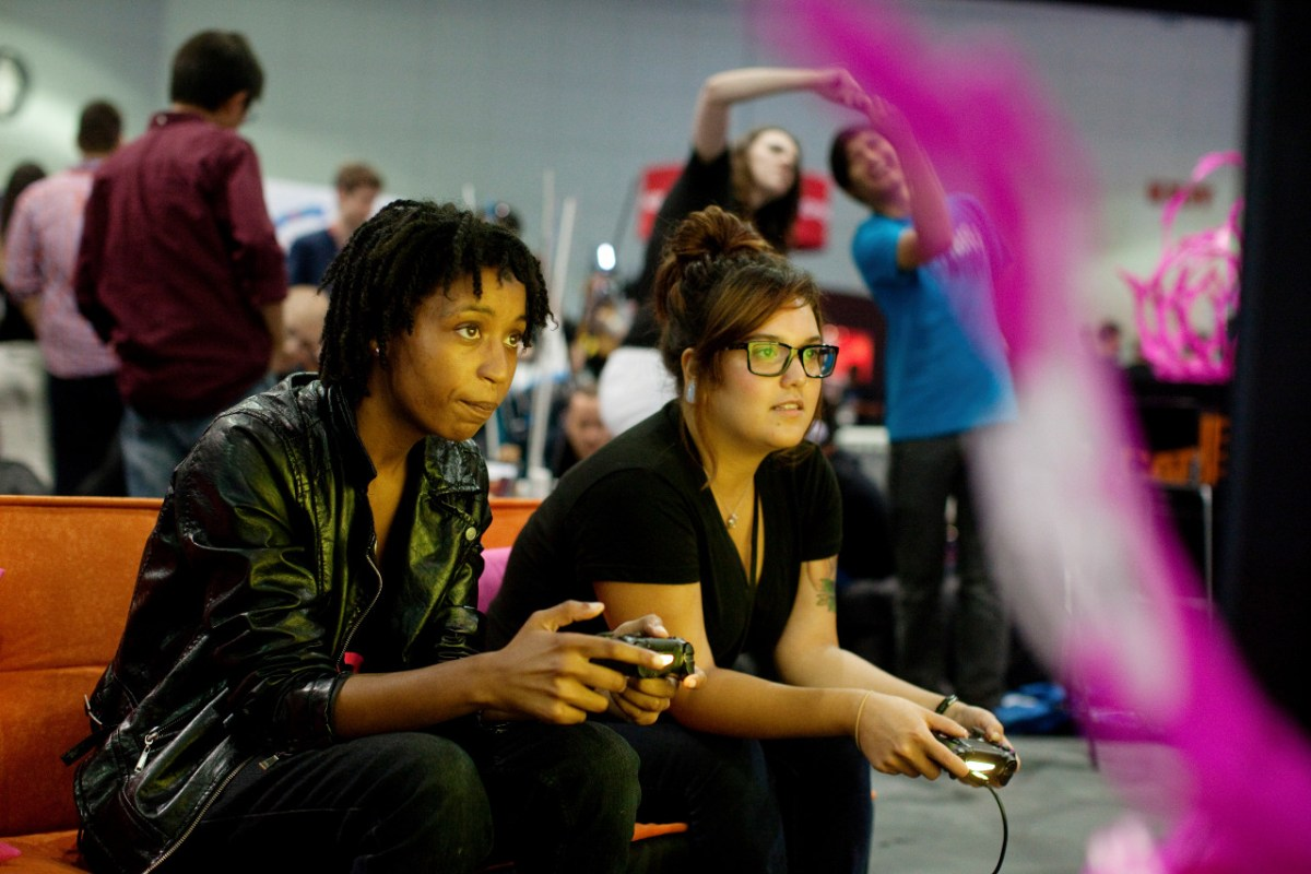 "** PHOTO MOVED IN ADVANCE AND NOT FOR USE - ONLINE OR IN PRINT - BEFORE DEC. 14, 2014. ** FILE — Tion Burton and Elaine Gomez, right, play a video game at the Electronic Entertainment Expo in Los Angeles, June 12, 2014. Where video games once had external enemies, the biggest threat to the culture now seems to come from within, in the form of the harassment of women gamers and creators, and the uproar over ""GamerGate."" (Emily Berl/The New York Times)"