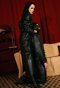 Beautiful Liza in Leather Coat and High Heel Boots Trains a hooded slave