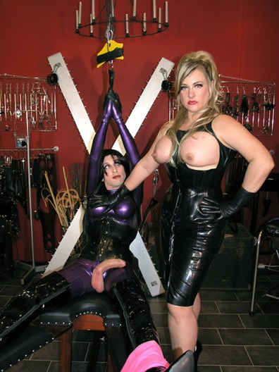 Cruel Blond Mistress in Latex Restrains and Tortures a sissified slave