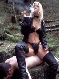 Cruel Mistress in Lingerie Smokes and Uses a slave as a Chair Outside