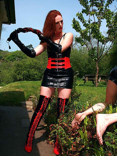 Redhead Mistress in PVC Outfit Whips a slave in the Garden