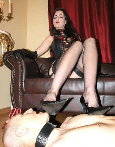 Sexy Dominatrix in Corset and Stockings Gets Her Feet Licked by a slave