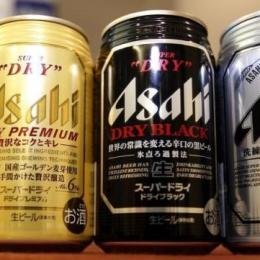 Asahi Breweries' new beer product Asahi Super Dry Premium (L), and reissued beers Asahi Super Dry (R) and Asahi Super Dry Dry Black are seen in front of its president Akiyoshi Koji during their unveiling in Tokyo December 12, 2013.  REUTERS/Yuya Shino