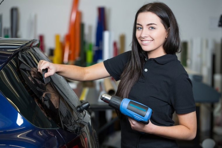 Female mechanic doing car wrapper tinting