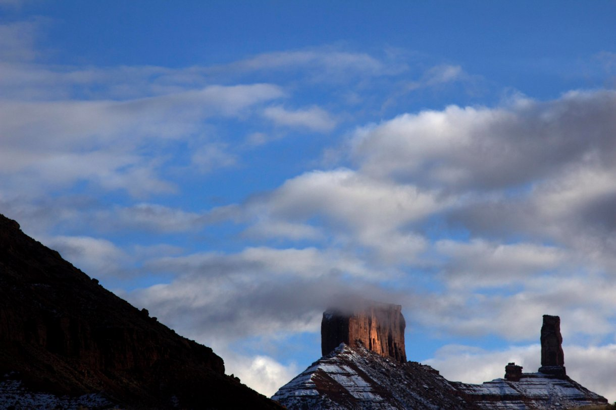 Clouds graze the top of snow-dusted mesas