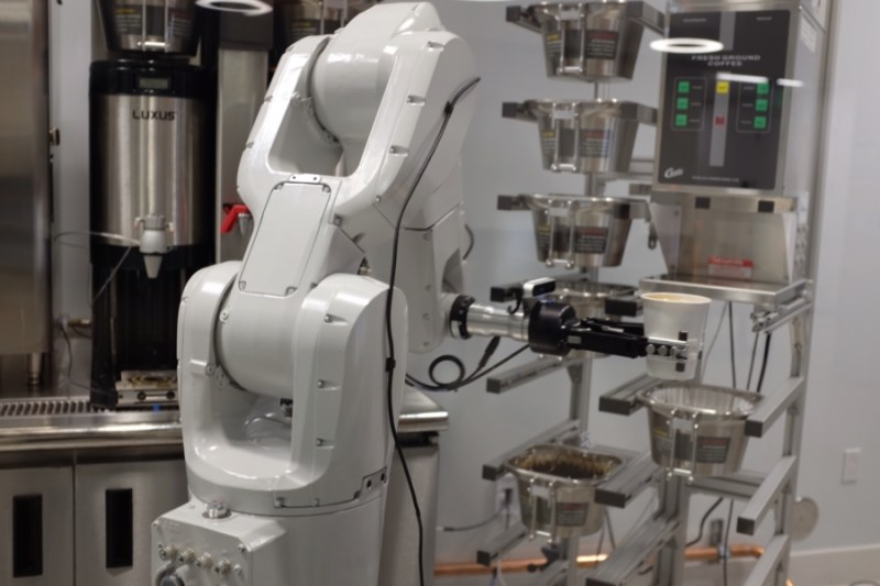 A robot arm holds a filled coffee cup