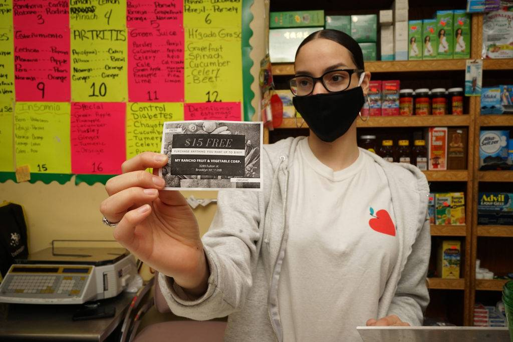Laury Paulino, former CHCCC student, holds one of the homemade vouchers for her parents new grocery store. Photo by Russell Frederick.