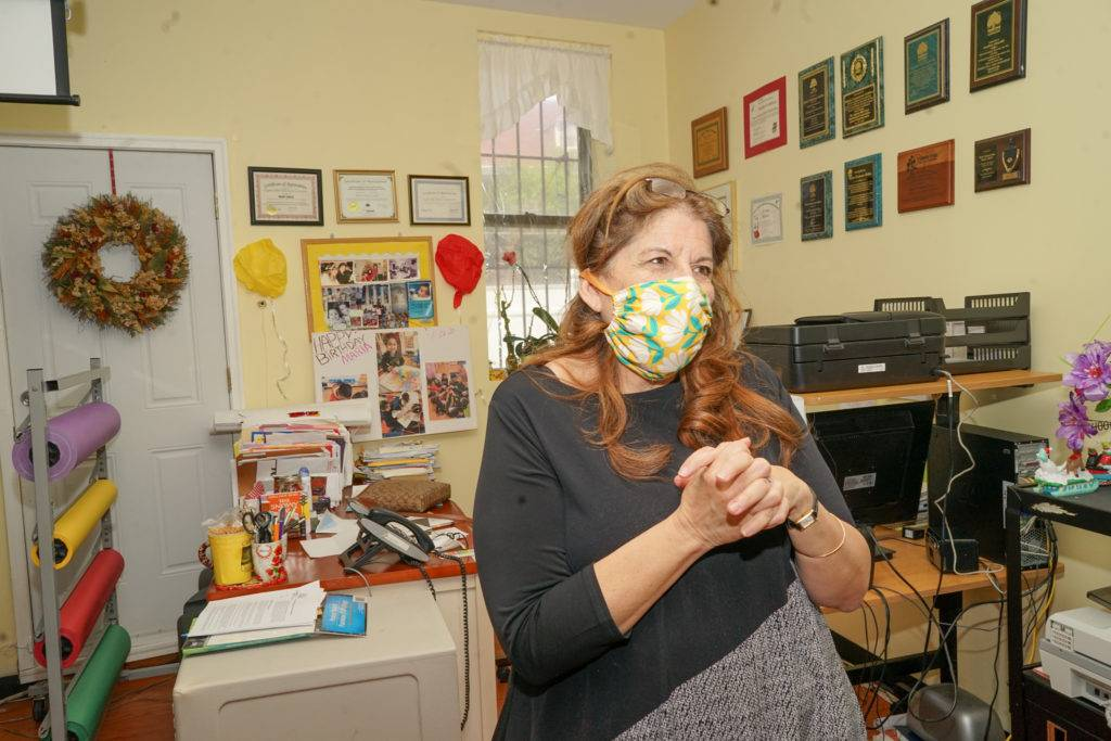 Maria Collier, director of the Cypress Hills Child Care Corporation, stands in front of her desk. Photo by Russell Frederick.