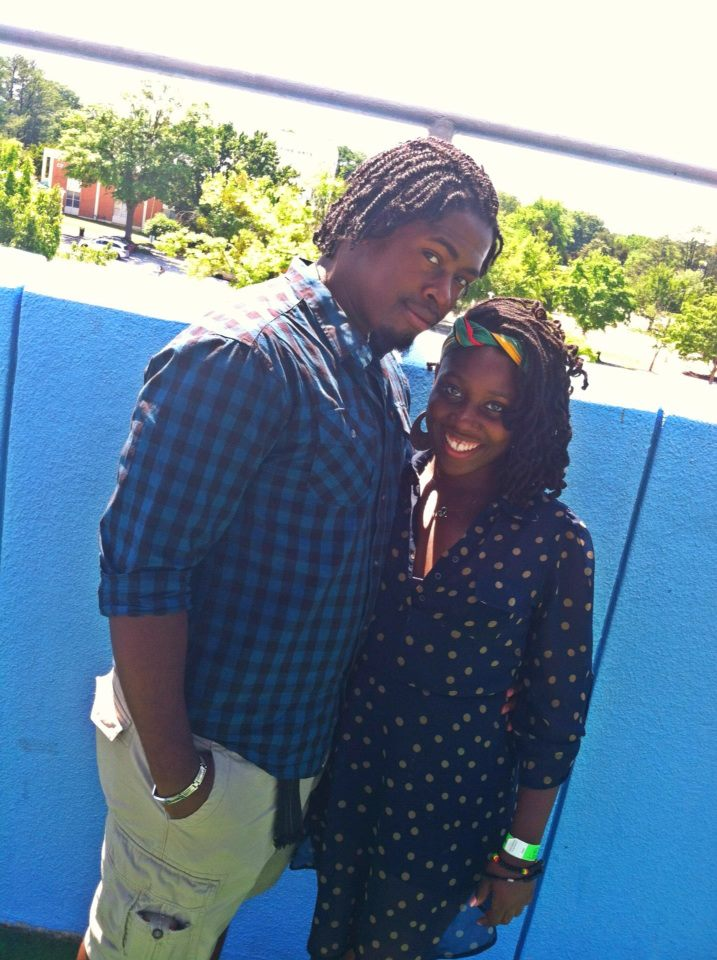 African-American Couple standing side by side and taking a photo outside. Man is in blue plaid shirt and woman is in blue polka dotted dress.