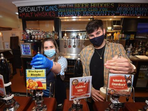 Jade Benson and Joe Cooper pulling pints in the Brew Room.