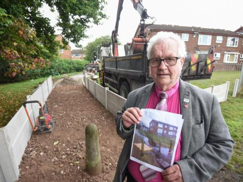 Grange resident Terry Bennett with his photograph of the flooding which he says people have been putting up with for 25 years