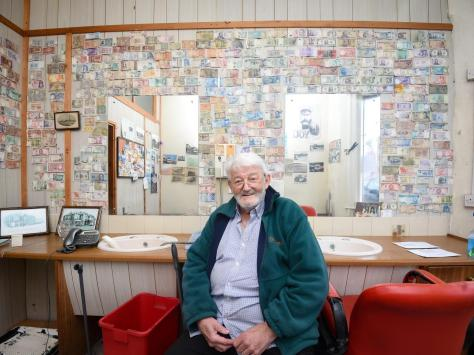 Barber Stuart Taylor is retiring after 30 years and plans to auction the collection of foreign money on his wall for charity.