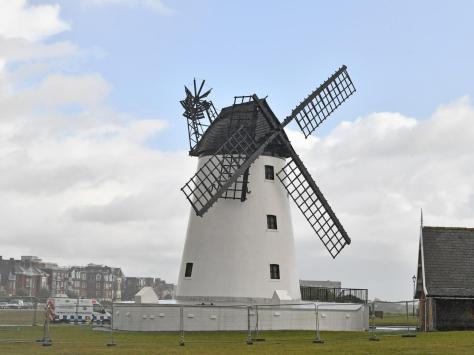 Lytham Windmill with its broken sail, cordoned off with fencing