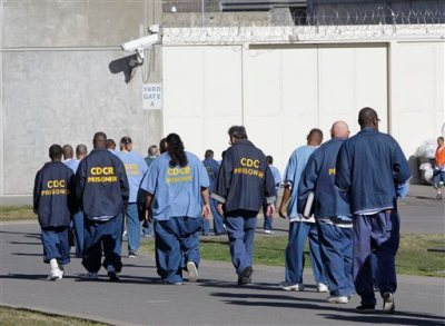 In this photo taken Tuesday, Feb. 26, 2013, inmates walk through the exercise yard at California State Prison Sacramento, near Folsom, Calif. The Supreme Court rejected California's appeal of a lower court order that could force the state to release thousands of California prison inmates before they complete their sentences, Tuesday, Oct. 15, 2013.(AP Photo/Rich Pedroncelli, file)