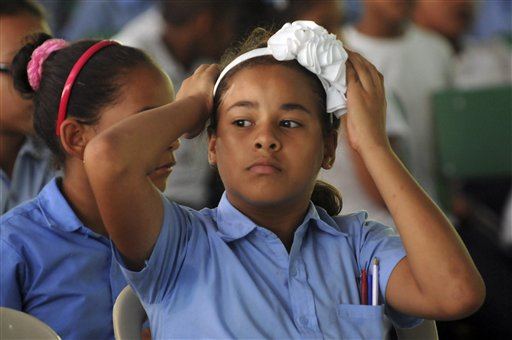 "In this Sept. 27, 2013 photo, 10-year-old Germaris Hernandez adjusts her headband as she watches a theater performance by the company ""Arbol Maravilloso"" or ""Wonderful Tree"" that that encourages black children to wear their hair natural instead of straightening it, through a fairy tale story, in Moca, Dominican Republic. The theater group has visited schools across the country to spread the word among black children that their features and heritage should be a source of pride. (AP Photo/Manuel Diaz)"