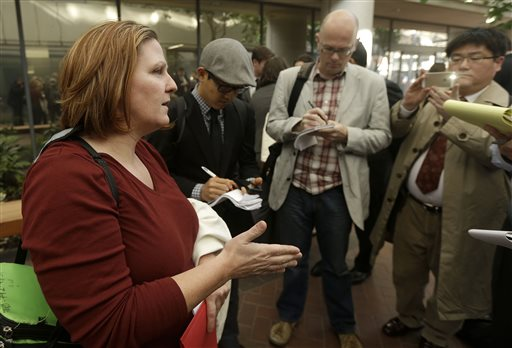 Jury foreperson Colleen Allen, left, speaks to reporters outside of the federal building in San Jose, Calif., Thursday, Nov. 21, 2013. A Silicon Valley jury on Thursday ordered Samsung Electronics to pay Apple $290 million for copying vital iPhone and iPad features. The verdict covers 13 older Samsung devices that a previous jury found were among 26 Samsung products that infringed Apple patents. (AP Photo/Jeff Chiu)