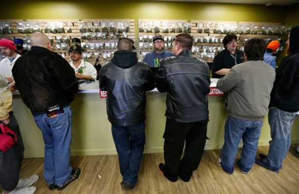 In this Jan. 1, 2014 file photo, employees help customers at the crowded sales counter inside the Medicine Man marijuana retail store, in Denver. A group of marijuana activists want another pot vote in Colorado, to loosen restrictions on who can have it. A proposed ballot measure up for state review Wednesday Jan. 14, 2014 would end criminal penalties for cannabis possession. If approved, the measure would effectively discard Colorado's 1-ounce possession limit and 21-and-over restriction. (AP Photo/Brennan Linsley, File)