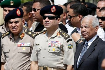 In this Friday, Sept. 20, 2013 file photo, Egypt's Defense Minister Gen. Abdel-Fattah el-Sissi, center, Egyptian Prime Minister Hazem el-Beblawi, right, and army's Chief of Staff Lt. Gen. Sedki Sobhi, left, attend the funeral of Giza Police Gen. Nabil Farrag in Cairo, Egypt. (AP Photo/Hassan Ammar, File)