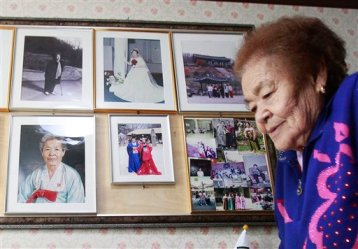 n this Feb. 3. 2014, Kim Gun-ja, 89, former comfort woman who was forced to serve for the Japanese troops as a sex slave during World War II, passes by her wedding picture, top center, at the House of Sharing, a nursing home and museum for 10 former sex slaves, in Toechon, South Korea. (AP Photo/Ahn Young-joon)