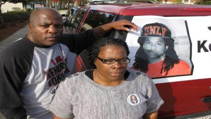 Kenneth and Jacquelyn Johnson stand next to a banner on their SUV showing their late son, Kendrick Johnson, on Dec. 13, 2013, in Valdosta, Ga.(AP PHOTO/RUSS BYNUM)