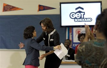 First Lady Michelle Obama hugs T.C. Williams High School student Edom Tesfa as she arrives to speak to students at the school in Alexandria, Va., Wednesday, Feb. 5, 2014, during a workshop to help students fill out the Free Application for Federal Student Aid. Mrs. Obama told students that filling out the FAFSA is a pivotal step toward finishing their education beyond high school. (AP Photo/Susan Walsh)