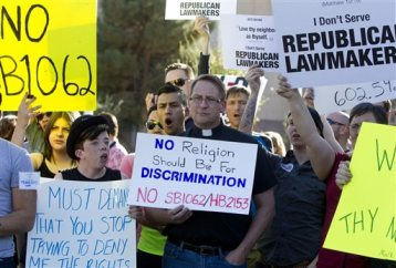 Opponents of the SB1062, a religious freedom bill, Ryan Ebersole, of Mesa, and Rev. Stephen Govett, of Glendale, urged Gov. Brewer to veto the bill during a protest rally Friday, Feb. 21, 2014, at the state Capitol. (AP Photo/The Arizona Republic, Cheryl Evans)