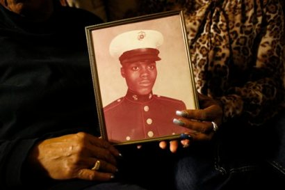 In this March 12, 2014 photo, a picture of Jerome Murdough is held by his mother Alma Murdough left, and sister  Cheryl Warner at Alma  Murdough's home in the Queens borough of New York.  Jerome Murdough, a mentally ill, homeless former Marine arrested for sleeping in the roof landing of a New York City public housing project during one of the coldest recorded winters in city history, died last month in a Rikers Island jail cell that multiple city officials say was at least 100 degrees when his body was discovered.  Murdough, 56, was found dead in his cell in a mental observation unit  in the early hours of Feb. 15, after excessive heat, believed to be caused by an equipment malfunction, redirected it's flow to his upper-level cell, the officials said.  (AP Photo/Jason DeCrow)