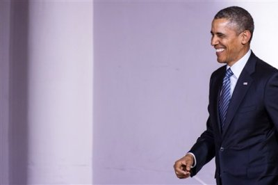 U.S. President Barack Obama smiles as he arrives for a speech at The Centre for Fine Arts in Brussels on Wednesday, March 26, 2014. (AP Photo/Geert Vanden Wijngaert)
