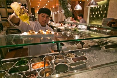 In this Dec. 5, 2013 file photo  a dish is prepped at the Fig & Olive restaurant, near New York's Rockefeller Center, in New York. The Commerce Department releases fourth-quarter gross domestic product on Thursday, March, 27, 2014.  (AP Photo/Richard Drew, File)
