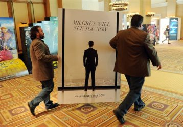 "Sheldon Domke, left, and Adam Mast move an advertisement for the upcoming film ""Fifty Shades of Grey"" during the second day of  CinemaCon 2014 on Tuesday, March 25, 2014 in Las Vegas. The film is set for release Valentine's Day of 2015. (Photo by Chris Pizzello/Invision/AP)"
